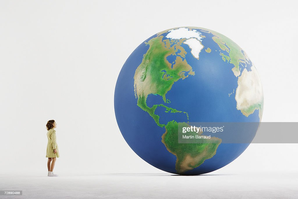Girl (8-9) standing in empty white room, looking at huge globe (digital enhancement) : Stock Photo