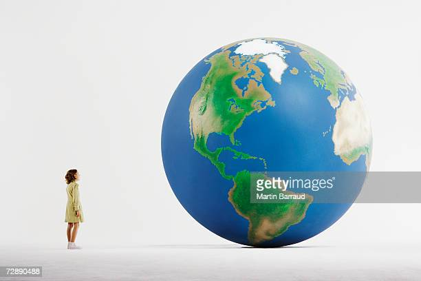 Girl (8-9) standing in empty white room, looking at huge globe (digital enhancement)
