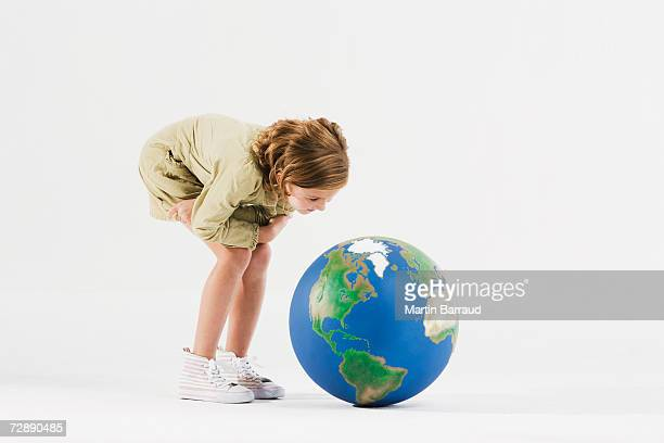 Girl (8-9) standing in empty white room, peering at globe