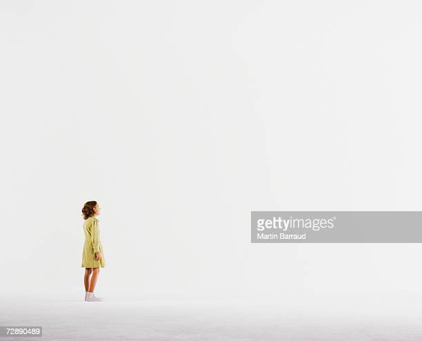 Girl (8-9) standing in empty white room
