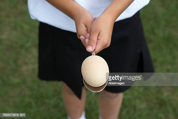 Girl (5-7) standing in field holding egg on spoon, mid section