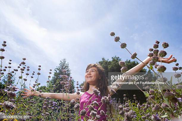 Girl (12-13 years) standing in field of flowers, low angle view