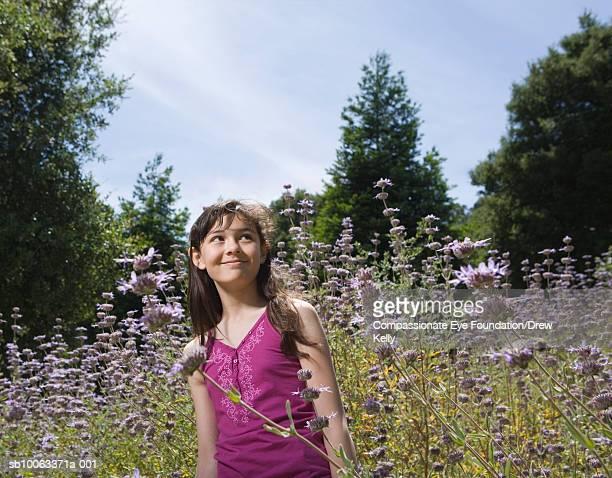 Girl (12-13 years) standing in field of flowers