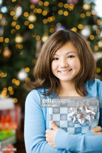 A girl standing in front of a Christmas tree holding a parcel.