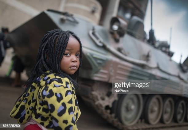 A girl standing in front of a military vehicle in the streets of the capital Harare Zimbabwe on 19 November 2017 a day after huge crowds rallied...