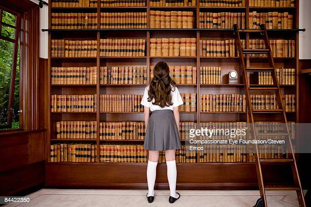 Girl standing in front of bookshelves in library