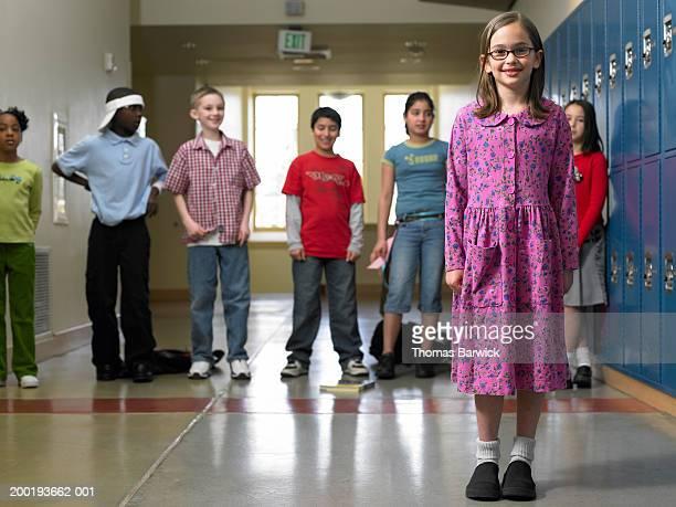 Girl (8-10) standing in front of classmates in school hallway