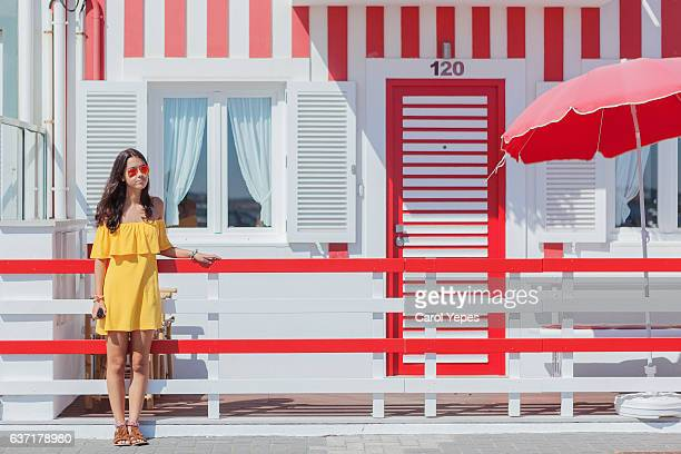 girl standing in front of colorful houses.Costa Nova, Aveiro, Portugal