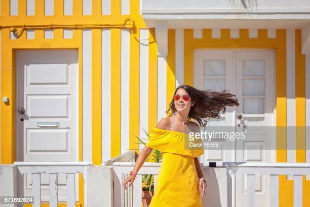 girl standing in front of colorful houses.costa nova, aveiro, portugal - traditionally portuguese stock pictures, royalty-free photos & images
