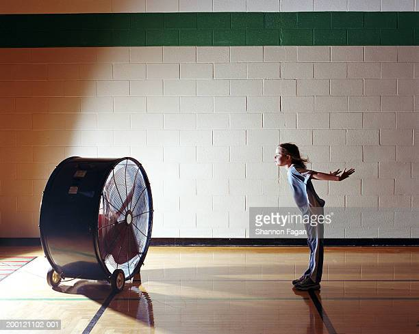 Girl (8-10) standing in front of large floor fan in gym, side view