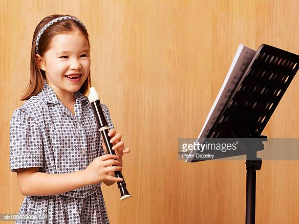 girl (6-7 years) standing in front of music stand holding recorder - recorder musical instrument stock photos and pictures