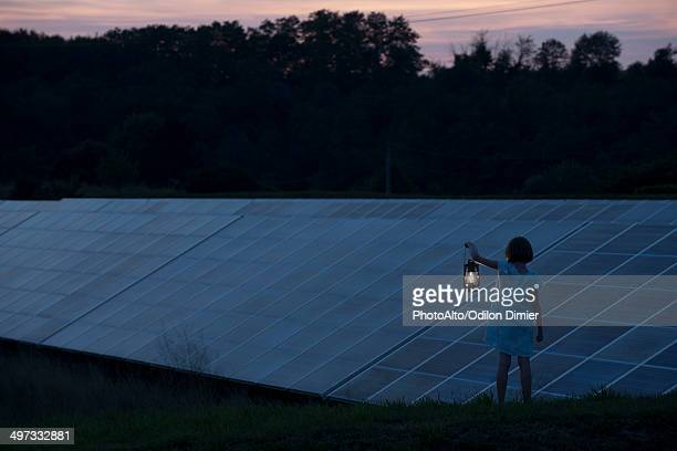 Girl standing in front of solar panels at twilight with old-fashioned lantern in hand