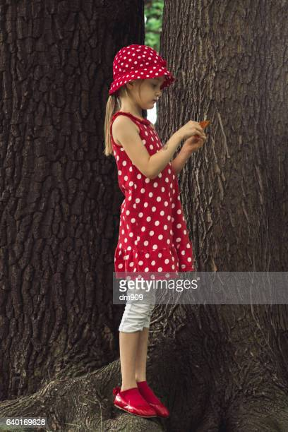 girl standing in front of trees