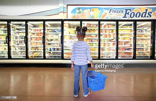 girl standing in frozen food section. - comida congelada - fotografias e filmes do acervo