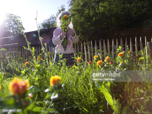 Girl (3-5) standing in garden holding bunch of flowers up to face