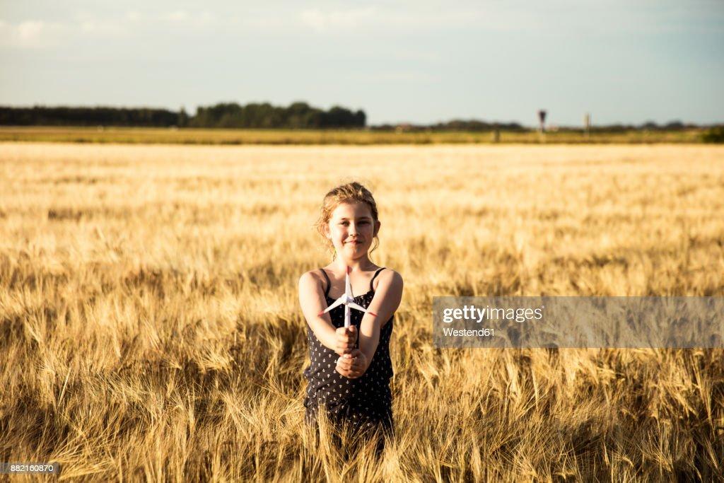 Girl standing in grain field holding miniature wind turbine : Stock-Foto