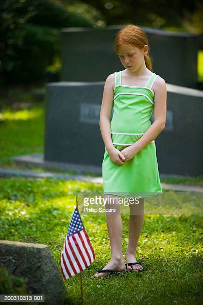 Girl (9-11) standing in graveyard, looking at tomb stone