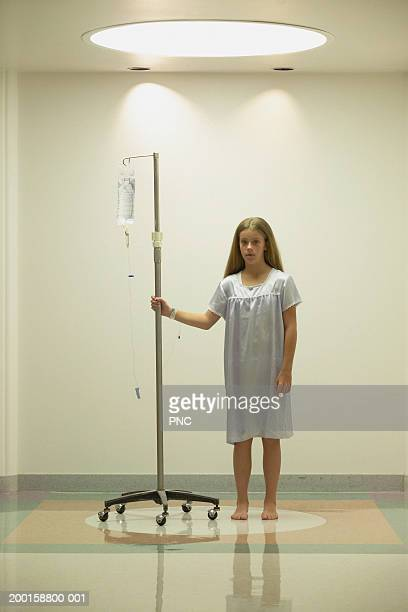 girl (11-13) standing in hospital corridor with iv drip, portrait - nightdress stock pictures, royalty-free photos & images