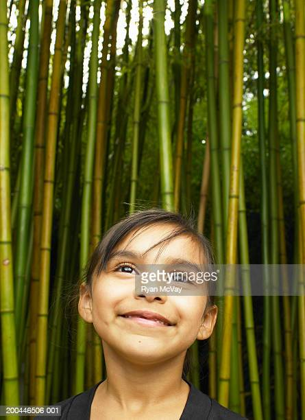 girl (5-7) standing in japanese timber bamboo grove, looking up - grove_(nature) stock pictures, royalty-free photos & images