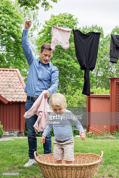 Girl standing in laundry basket while father removing clothes from clothesline
