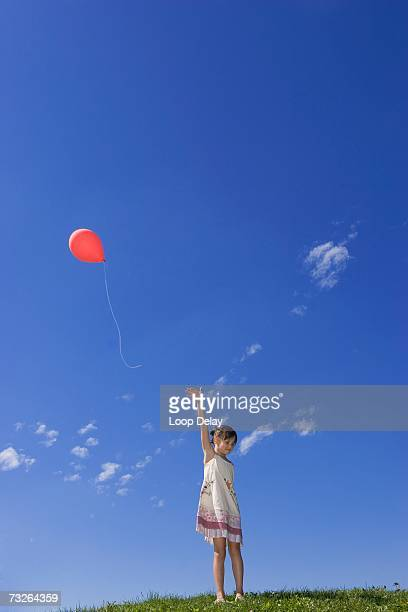 Girl (7-9) standing in meadow, releasing balloon