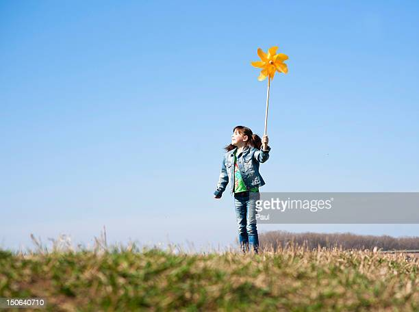 Girl standing in meadow with toy windmill