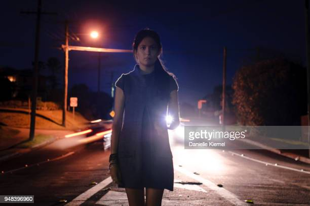 girl standing in middle of road at night, front view - en medio de la carretera fotografías e imágenes de stock