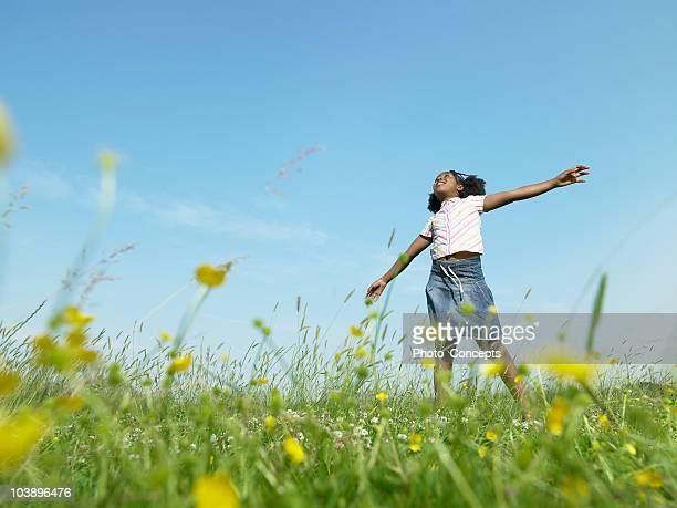 girl standing in open field - wildflower stock pictures, royalty-free photos & images