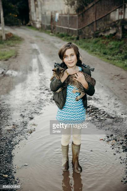 Girl standing in puddle holding kitten