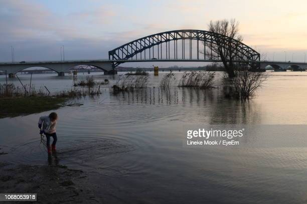 girl standing in river against bridge during sunset - zwolle stock pictures, royalty-free photos & images