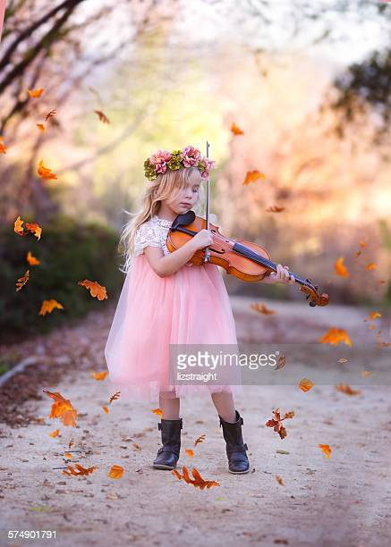 Girl standing in road playing the violin with leaves falling all around