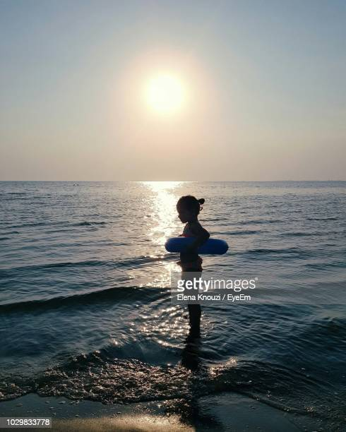 girl standing in sea against sky during sunset - elena knouzi stock pictures, royalty-free photos & images