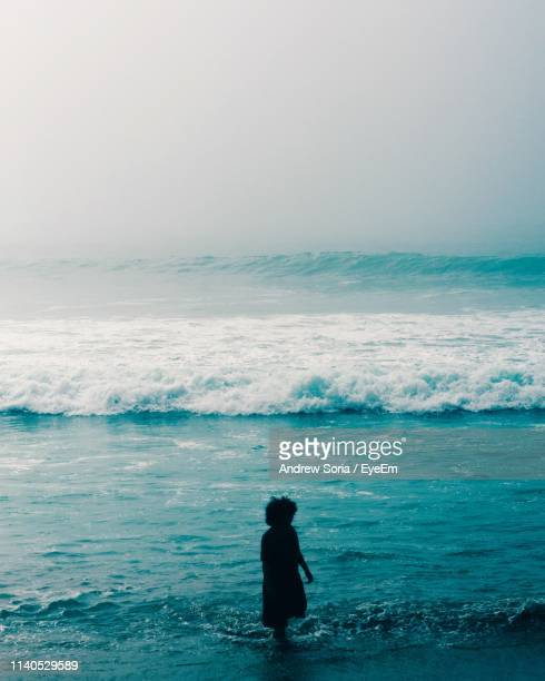 Girl Standing In Sea Against Sky