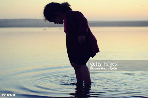 Girl Standing In Sea During Sunset