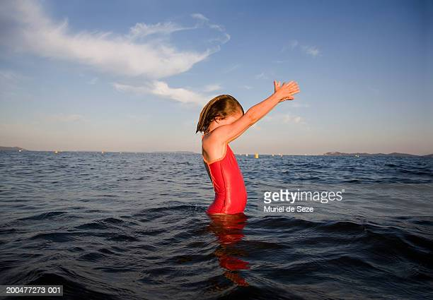 Girl (7-9) standing in sea preparing to dive, side view