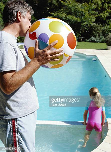 Girl (5-7) standing in shallow swimming pool, father holding ball