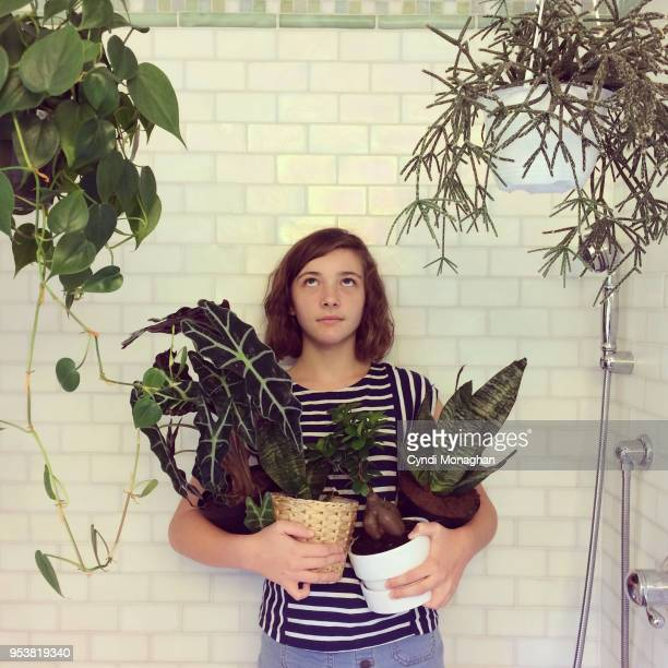 girl standing in shower with armful of houseplants - toilet planter stock pictures, royalty-free photos & images