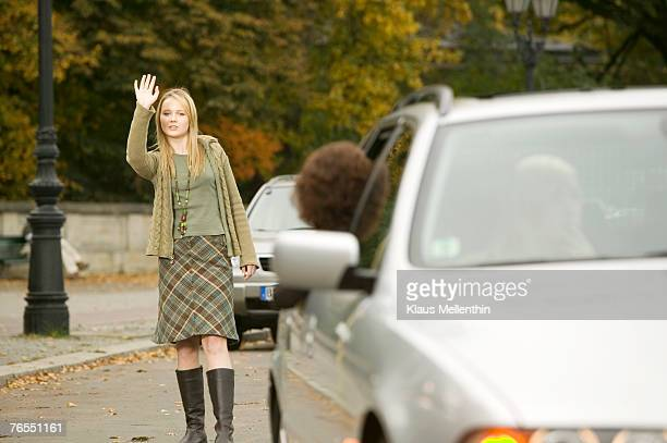 Germany, teenage girl (16-17) standing in street, waving hand