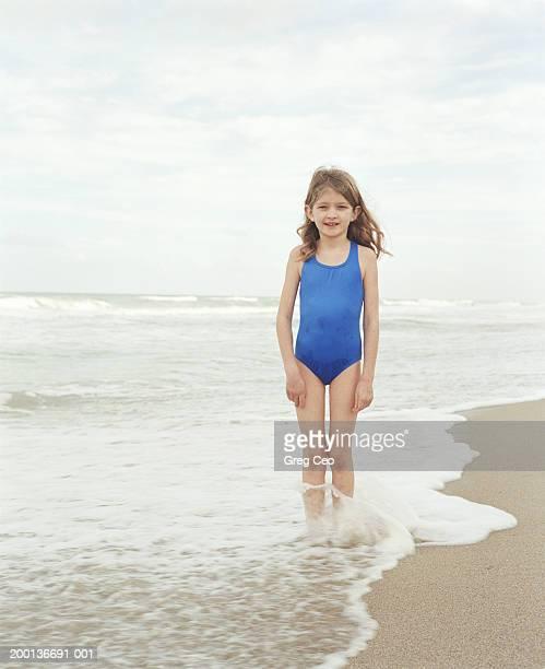 Girl (6-8) standing in surf, portrait