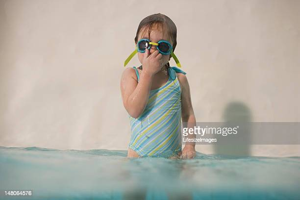 Girl (3-5) standing in swimming pool, wearing goggles and holdin