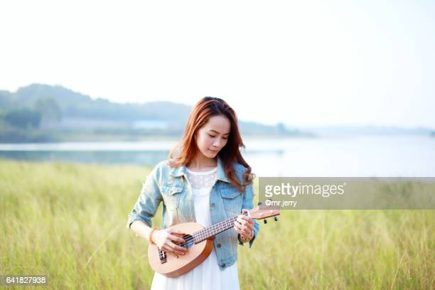 girl standing in the field with a ukelele - ukulele stock pictures, royalty-free photos & images