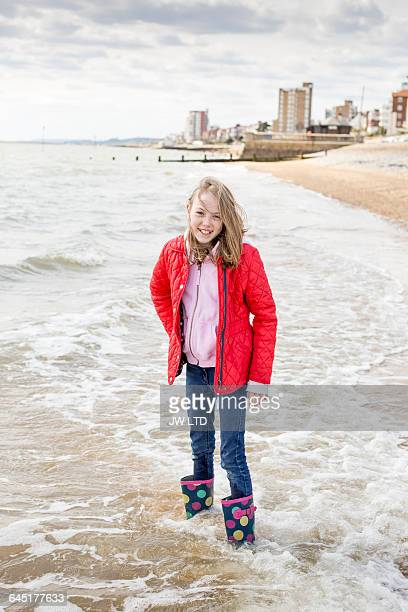 girl (8-9) standing in the sea - jacket stock pictures, royalty-free photos & images