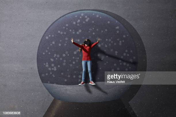 Girl standing inside imaginary painted Christmas snow globe