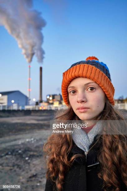 Girl standing near apartment block and power station smoke stacks, Oulu, Finland