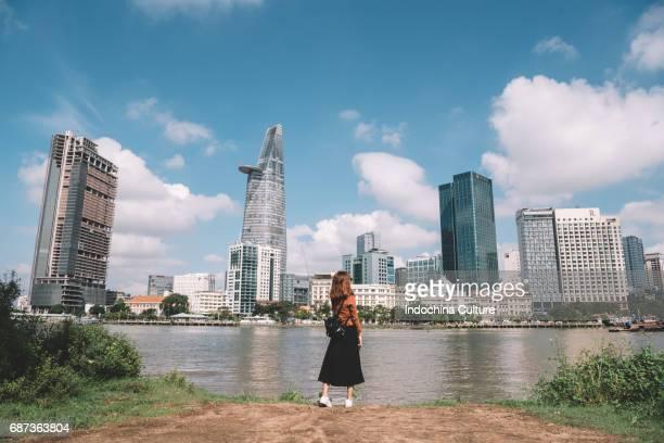 girl standing near by riverside with morden building on background - ho chi minhstad stockfoto's en -beelden