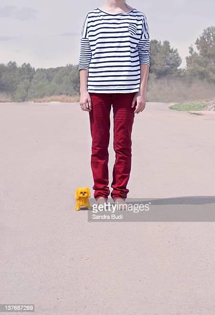 Girl standing near little yellow toy dog