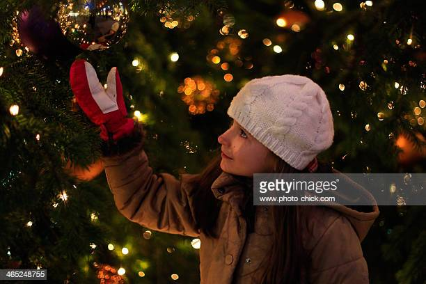 girl standing next to a Christmas tree