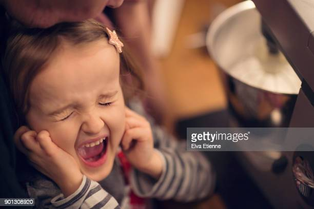girl (4-5) standing next to a noisy electric food mixer, with fingers in her ears, shouting - fingers in ears stock pictures, royalty-free photos & images