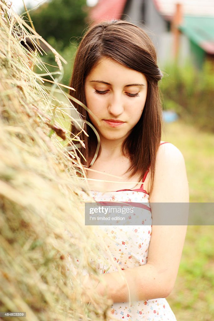 Girl standing next to a stack of hay being sad : Photo