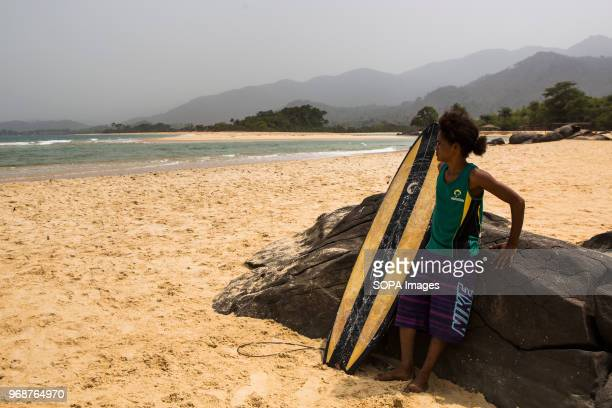 A girl standing next to a surf board on the beach In Bureh Beach 70 kilometers from Freetown there is a surfing camp where the kids forget the daily...
